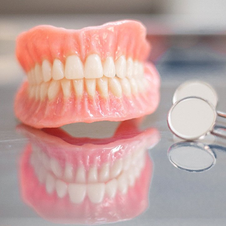Pair of dentures sitting on a reflective table