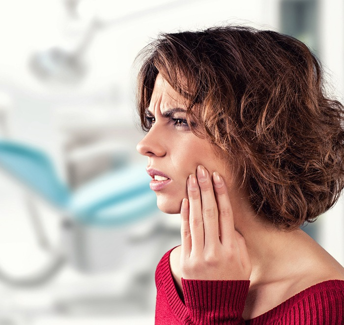 Woman in need of emergency dentistry holding cheeks in pain