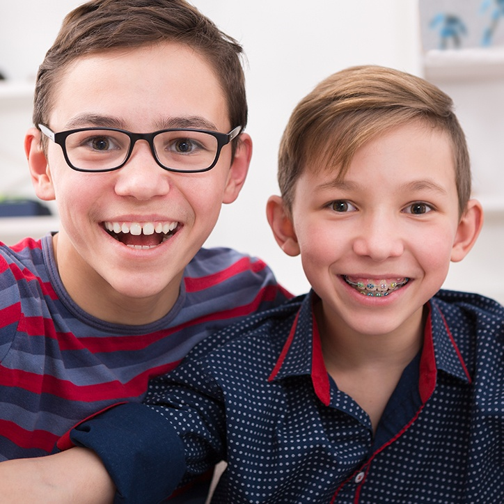Teen smiling after braces next to younger boy with metal braces