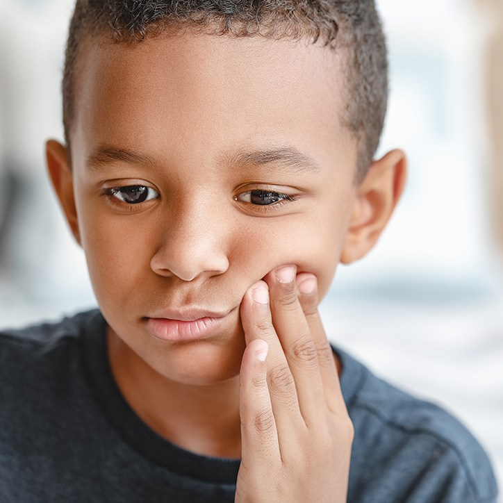 Young boy in need of treatment for orthodontic emergency holding his cheek