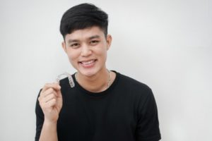 Man holding Invisalign in Long Beach for bite problems